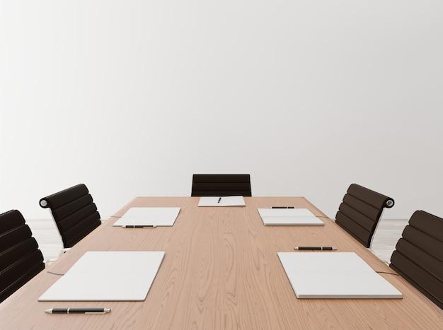 Chiuda sulla sala riunioni vuota con le sedie, la tavola di legno, il taccuino, il muro di cemento