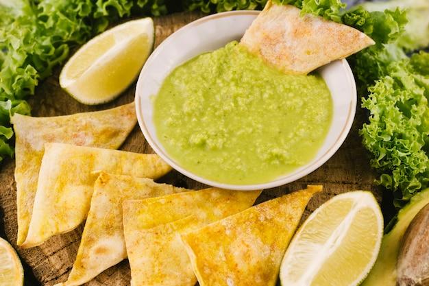 Chiuda sulla salsa e sui nachos del guacamole
