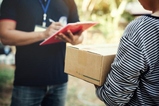 Chiuda sulla scatola della tenuta della donna con la consegna di servizio e tenendo un bordo