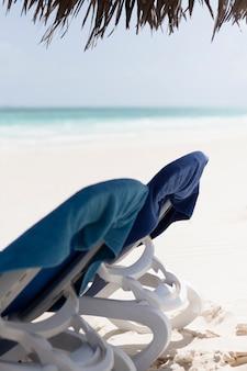 Chiuda sulla sedia di spiaggia di vista laterale alla spiaggia