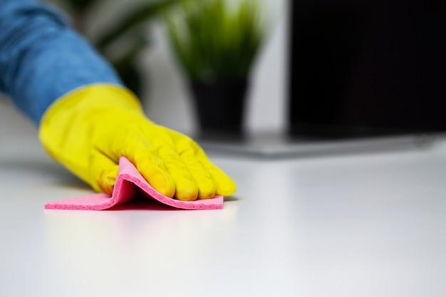 Chiuda sulla spugna della tenuta della mano del lavoratore della società di pulizia