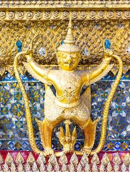 Chiuda sulla statua gigante tailandese alla pagoda dorata al grande palazzo, il tempio di emerald buddha (kaew di pra di wat) a bangkok, tailandia.