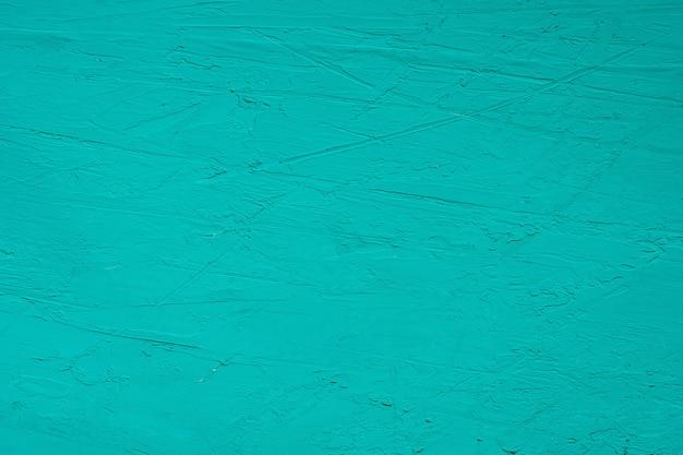 Chiuda sulla struttura della pittura di colore verde sulla parete del cemento.
