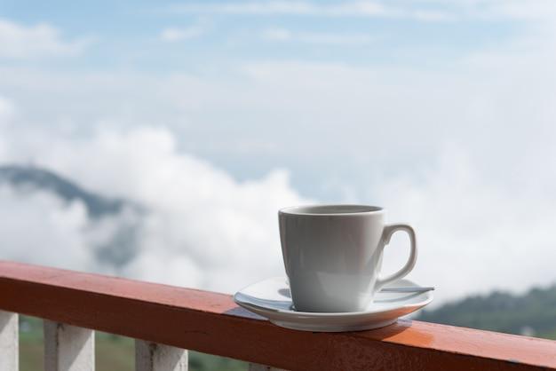 Chiuda sulla tazza bianca di caffè caldo sul bordo del balcone con fondo verde naturale all'aperto