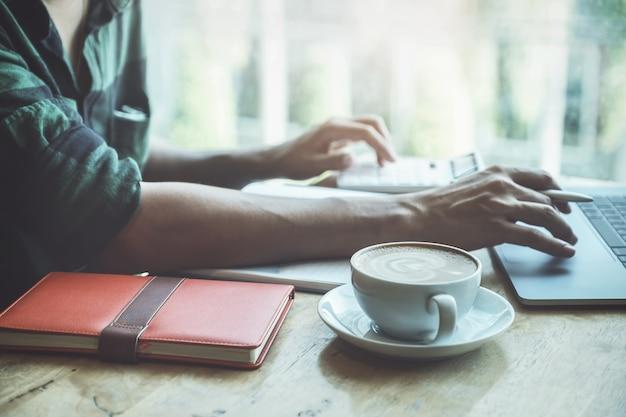 Chiuda sulla tazza di caffè con l'uomo di affari che per mezzo del computer portatile e del calcolatore calculatig per il bilancio di controllo o la finanza della sua società.