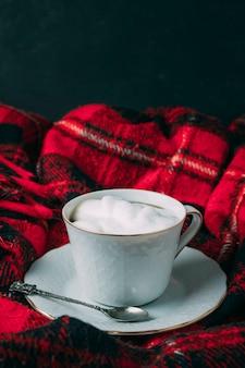 Chiuda sulla tazza di caffè con schiuma