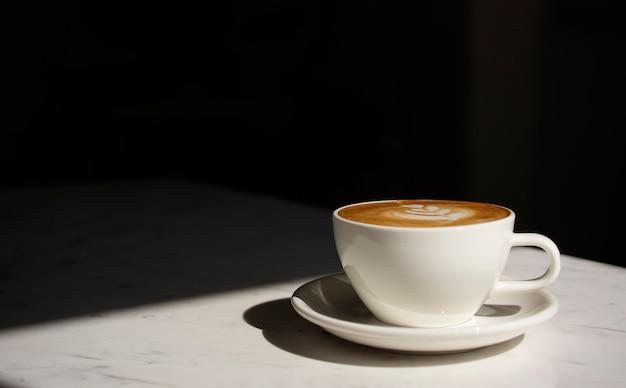 Chiuda sulla tazza di caffè del cappuccino con lo spazio della copia e scurisca il fondo