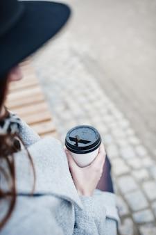 Chiuda sulla tazza di caffè di plastica per mano della ragazza di modello in un cappotto grigio e black hat che si siedono sul banco alla via della città.