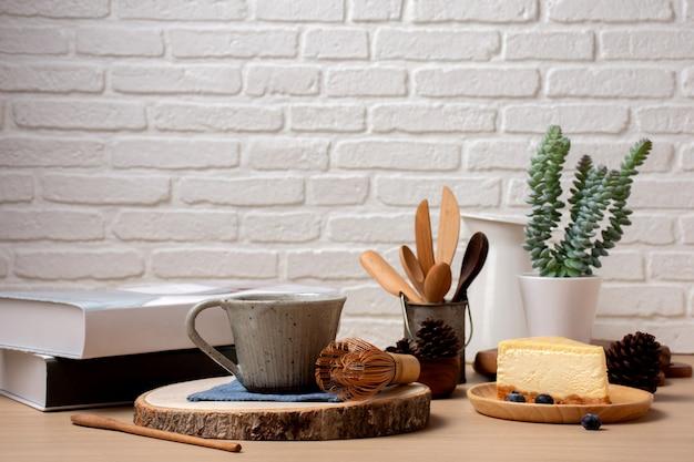 Chiuda sulla tazza di caffè e sulla torta del colpo con il libro sulla tavola in caffetteria