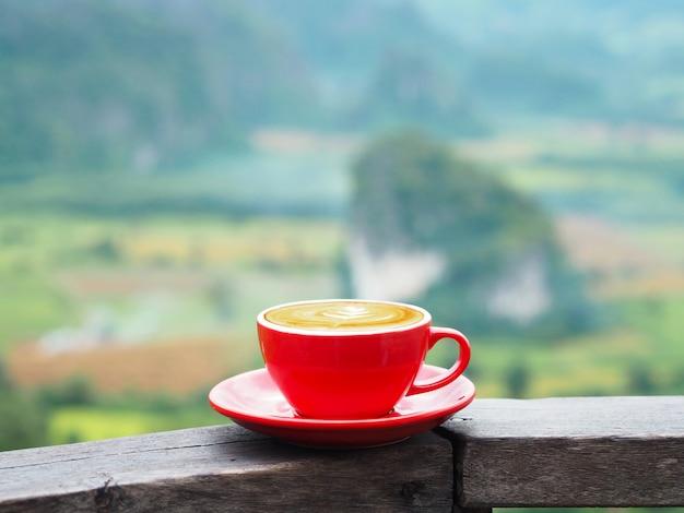 Chiuda sulla tazza rossa del caffè del latte sopra la montagna confusa