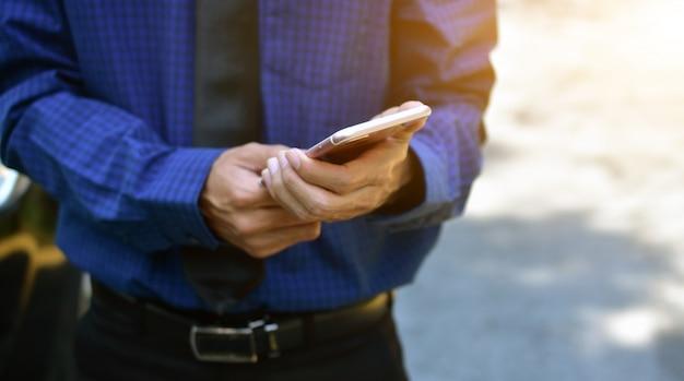 Chiuda sulla tecnologia mobile dello smart phone della tenuta dell'uomo d'affari