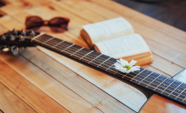 Chiuda sulla testa della chitarra classica con i vetri e il libro