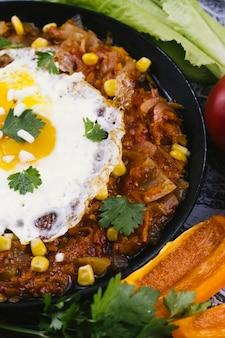 Chiuda sulla vaschetta con le uova e l'alimento messicano