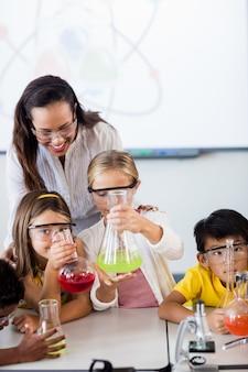 Chiuda sulla vista degli allievi che fanno la scienza con l'insegnante