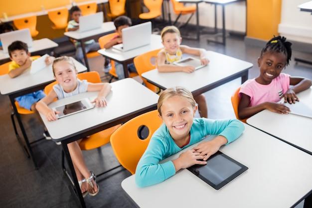 Chiuda sulla vista degli allievi che studiano con il pc della compressa e del computer portatile