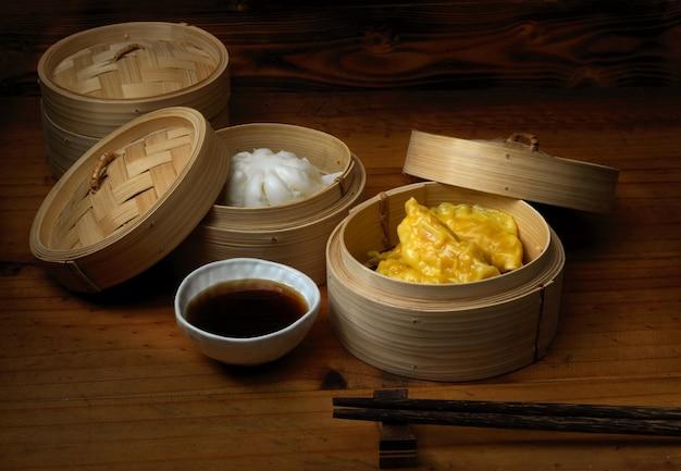 Chiuda sulla vista degli gnocchi cotti a vapore che servono sulla cucitrice di bambù in ristoranti cinesi