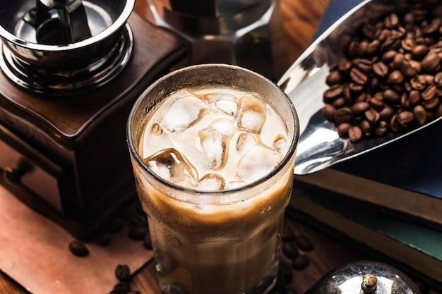 Chiuda sulla vista dei cubetti di ghiaccio in caffè preparato freddo in vetro su spazio scuro