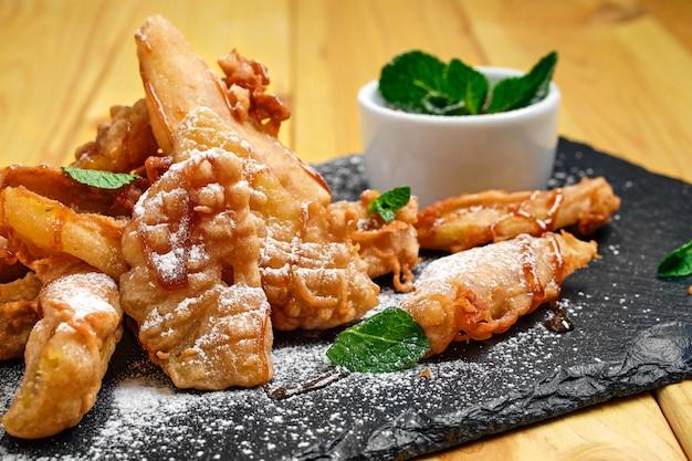 Chiuda sulla vista dei frutti fritti nel grasso bollente nell'impanare servito con marmellata di fragole e del caramello