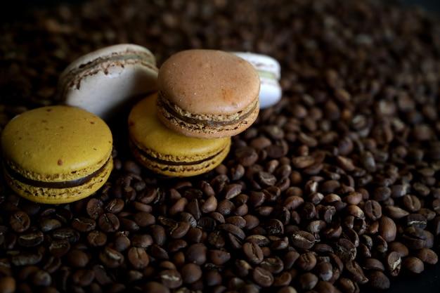 Chiuda sulla vista dei macarons del cioccolato e del caffè sul chicco di caffè