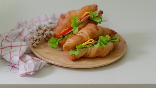 Chiuda sulla vista dei panini del croissant con il prosciutto e il formaggio sul piatto di legno