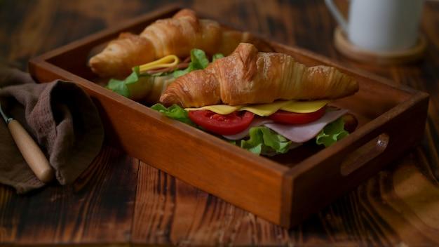 Chiuda sulla vista dei panini del croissant con il prosciutto e il formaggio sulla scatola della cassa di legno con il tovagliolo marrone
