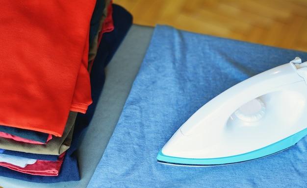 Chiuda sulla vista dei vestiti del ferro sulla tavola da stiro con la pila di camice rivestite di ferro