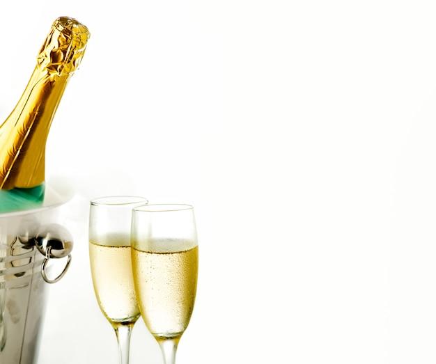 Chiuda sulla vista dei vetri e della bottiglia del champagne in secchiello del ghiaccio