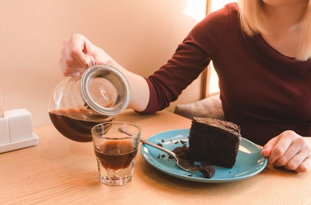 Chiuda sulla vista del caffè di versamento della donna nella tazza. pranzo di lavoro