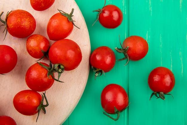 Chiuda sulla vista del modello dei pomodori sul tagliere su superficie verde