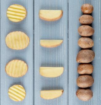 Chiuda sulla vista del modello delle patate affettate e intere su fondo di legno
