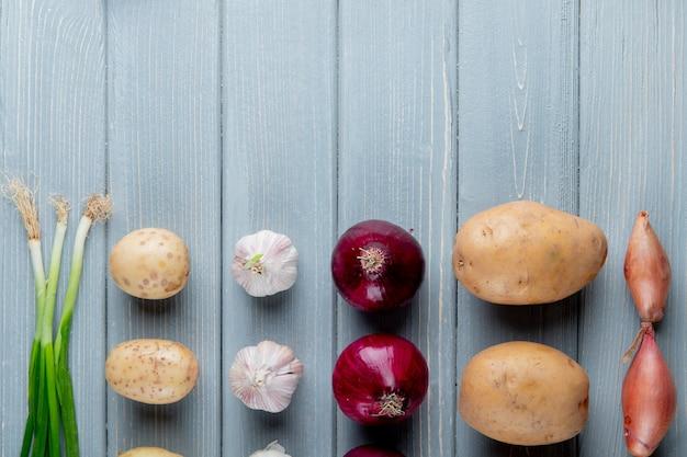 Chiuda sulla vista del modello delle verdure come cipolla dell'aglio della patata dello scalogno su fondo di legno con lo spazio della copia