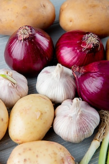 Chiuda sulla vista del modello delle verdure come patata dell'aglio della cipolla rossa su fondo di legno
