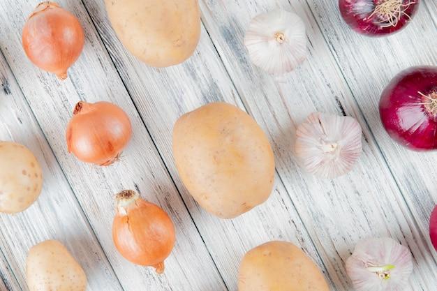 Chiuda sulla vista del modello delle verdure come patata dell'aglio della cipolla su fondo di legno