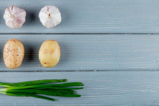Chiuda sulla vista del modello delle verdure come patata dell'aglio e cipolla verde su fondo di legno con lo spazio della copia