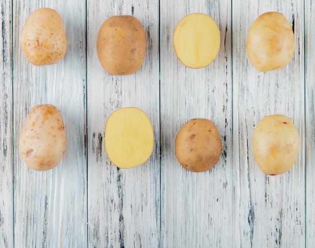 Chiuda sulla vista del modello di patate intere e tagliate su fondo di legno con lo spazio della copia