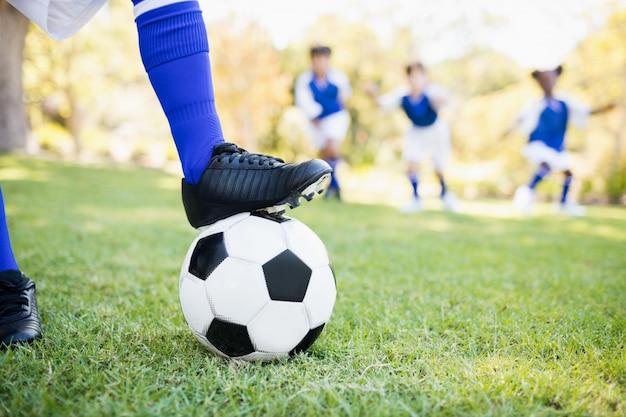 Chiuda sulla vista del pallone sotto le scarpe da calcio contro il gioco dei bambini
