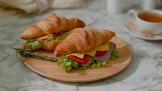 Chiuda sulla vista del pasto della prima colazione con il prosciutto e il formaggio dei panini del croissant sul piatto di legno e sulla tazza di tè