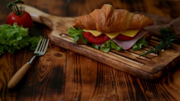 Chiuda sulla vista del pasto della prima colazione con il prosciutto e il formaggio del panino del croissant sul vassoio di legno