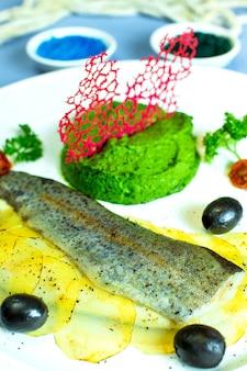 Chiuda sulla vista del pesce cotto a vapore con purea di broccoli e patate affettate e olive nere sul piatto bianco sul blu