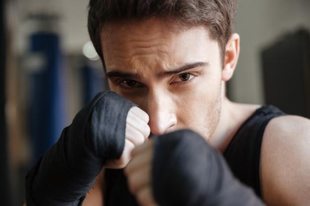 Chiuda sulla vista del pugile serio che fa l'esercizio in palestra