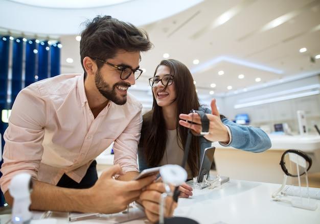 Chiuda sulla vista del ritratto di giovani coppie felici di amore dei pantaloni a vita bassa soddisfatti felici svegli che tengono e che provano i nuovi aggeggi astuti in un deposito di tecnologia.