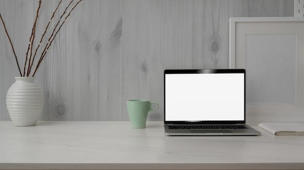 Chiuda sulla vista dell'area di lavoro alla moda con il computer portatile dello schermo in bianco sullo scrittorio di marmo con la parete rustica moderna bianca