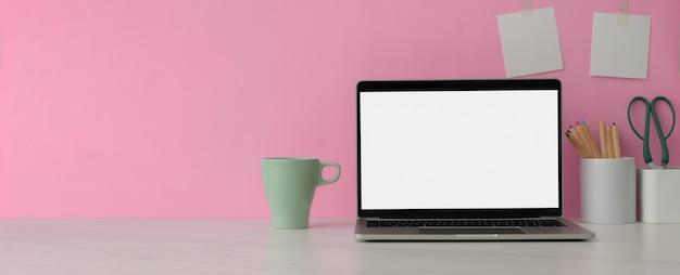 Chiuda sulla vista dell'area di lavoro con il computer portatile dello schermo in bianco, la tazza, i rifornimenti e copi lo spazio sulla tavola di marmo