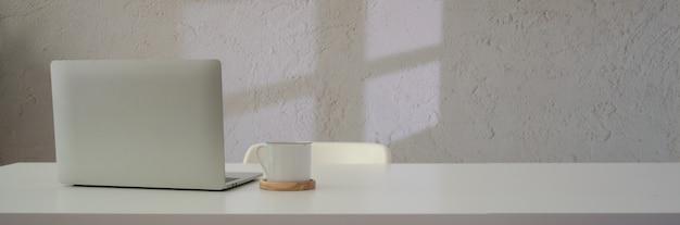 Chiuda sulla vista dell'area di lavoro con il computer portatile, la tazza di caffè e copi lo spazio sulla tavola bianca