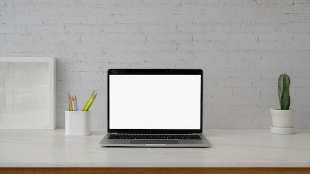 Chiuda sulla vista dell'area di lavoro minima con il computer portatile sullo scrittorio di marmo con la parete bianca bianca