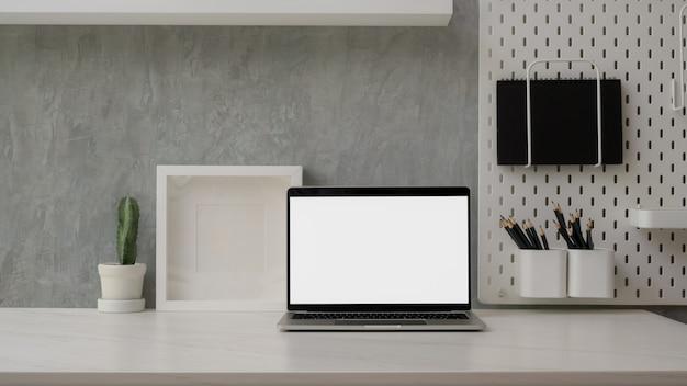 Chiuda sulla vista dell'area di lavoro moderna con il computer portatile dello schermo in bianco, le decorazioni e lo spazio della copia