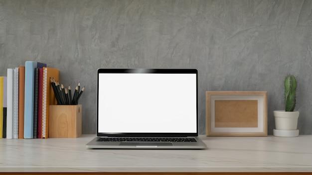 Chiuda sulla vista dell'area di lavoro moderna con il computer portatile, le decorazioni, i libri e la cancelleria dello schermo in bianco