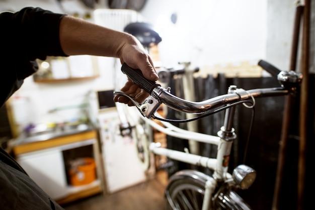 Chiuda sulla vista dell'uomo che controlla le rotture della bicicletta.