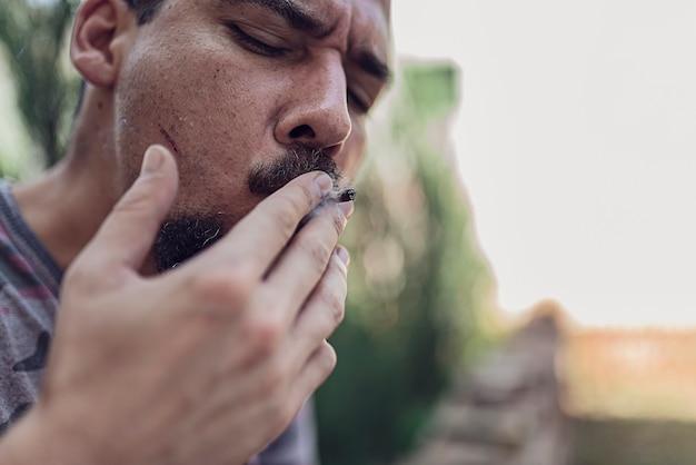 Chiuda sulla vista dell'uomo che fuma la sigaretta di marijuana all'aperto