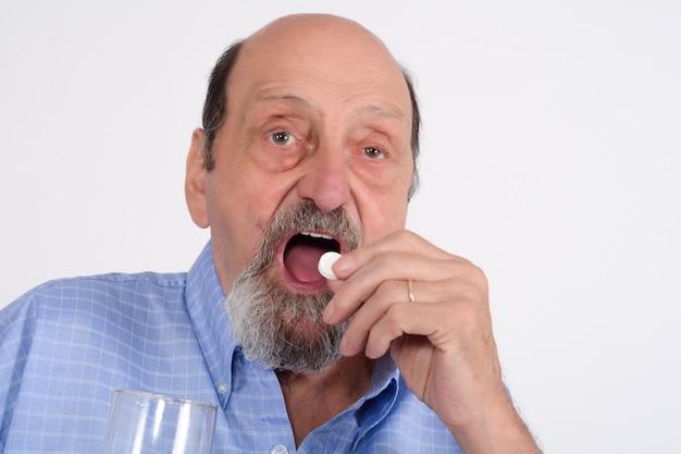 Chiuda sulla vista dell'uomo senior che prende la pillola